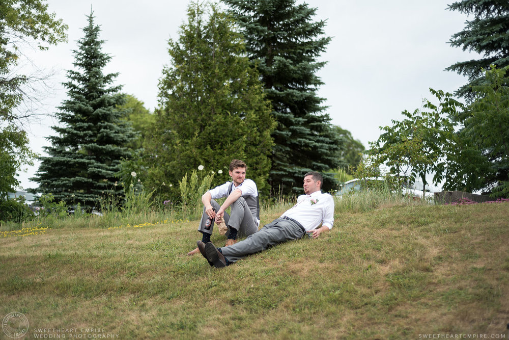 Groom and his best man relaxing on the grass; Aberfoyle Mill Wedding