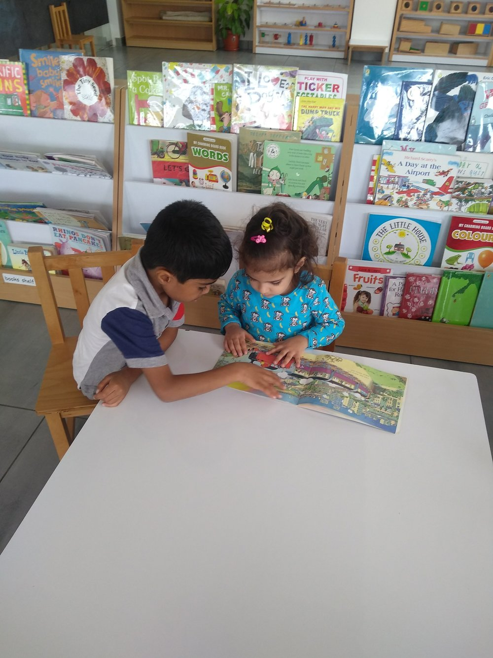 An older child helping a younger peer understand a story