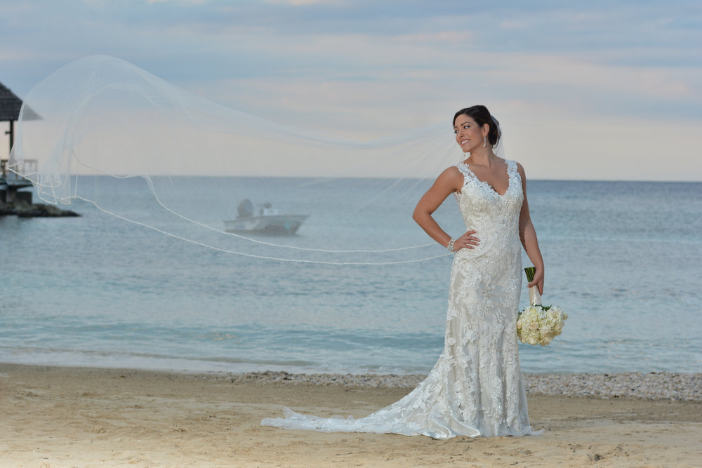 A stunning destination wedding photo on the beach is disrupted by a boat and pier in the background.