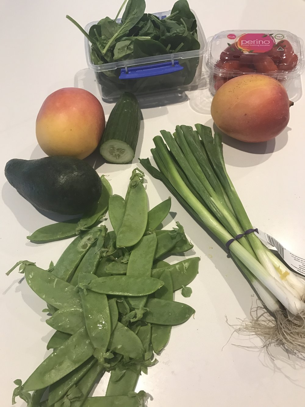 Chop up all ingredients - Avocado, Spring Onions, Cherry Tomatoes, Cucumber, Mangos, and Beans.  Add to spinach with your favourite dressing.  Have on it's own, or with toasted pine nuts.  For a larger meal, purchase a cooked chicken as chicken and mango salad goes well together.