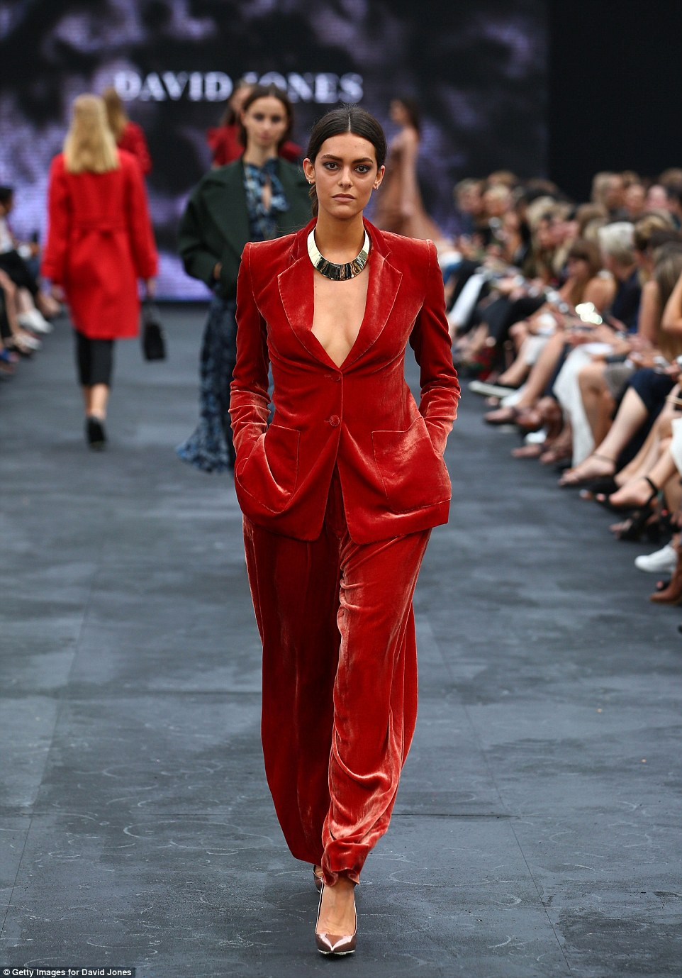 One striking ensemble by Bianca Spender featured a stunning red velvet suit with a daring neckline, paired with a chunky metallic necklace.   Photo
