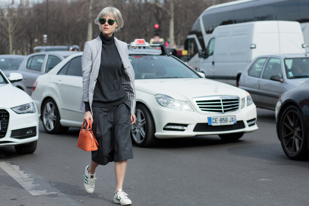 2015: Fashion Blogger Linda Tol wears Louis Vuitton bag, LK Bennett jacket, Dries Van Noten trousers, Uniqlo sweater, Adidas shoes, and Mykita sunglasses on day 5 of Paris Collections.  A style that would still be in vogue today and for many years.