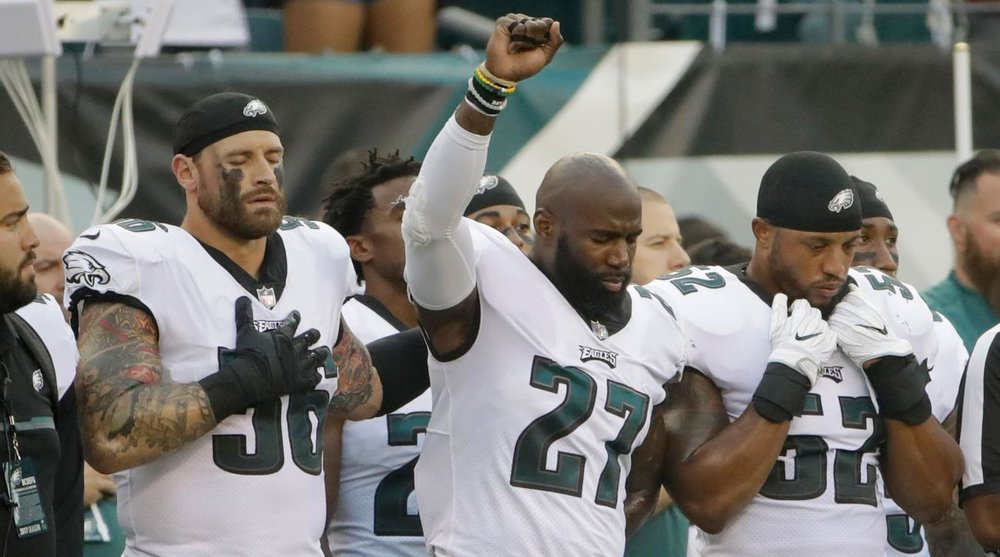 Photo Credit: Sports Illustrated. Jenkins (c.) hold his fist in demonstration as teammate Chris Long (l.) stands in solidarity.