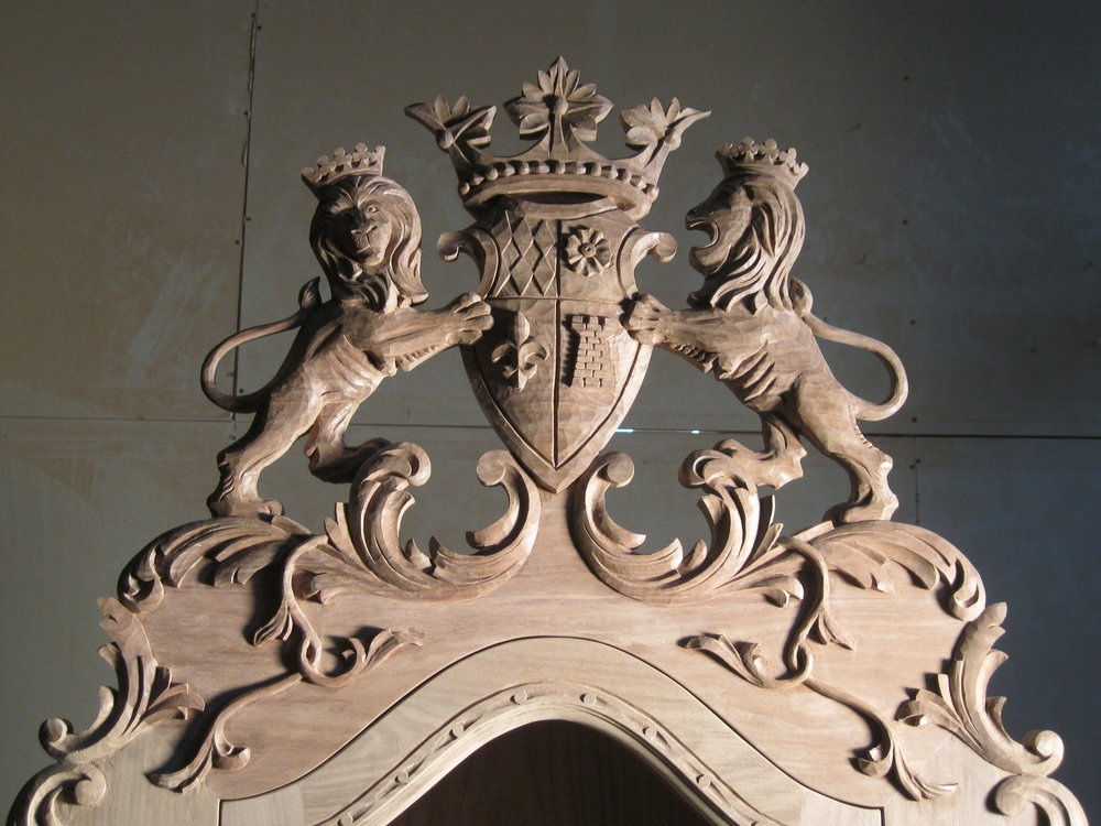 hand carved cabinet crest.