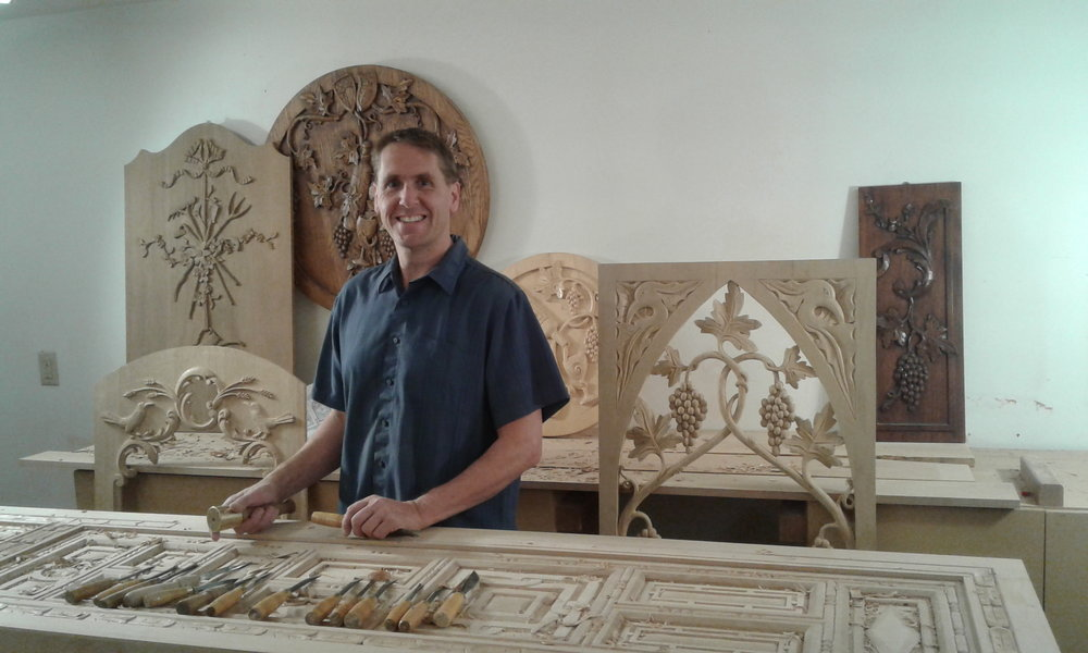 Erik with a collection of his wood carvings