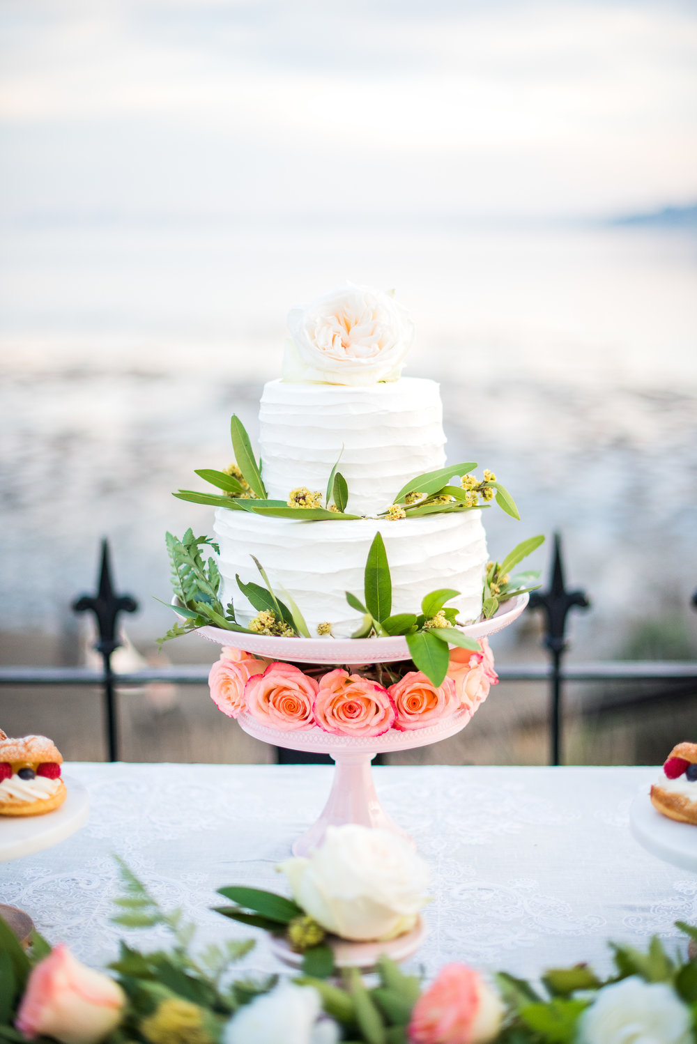 Two tiered textured buttercream cake adorned with greenery. Photo:  Yasmin Roohi
