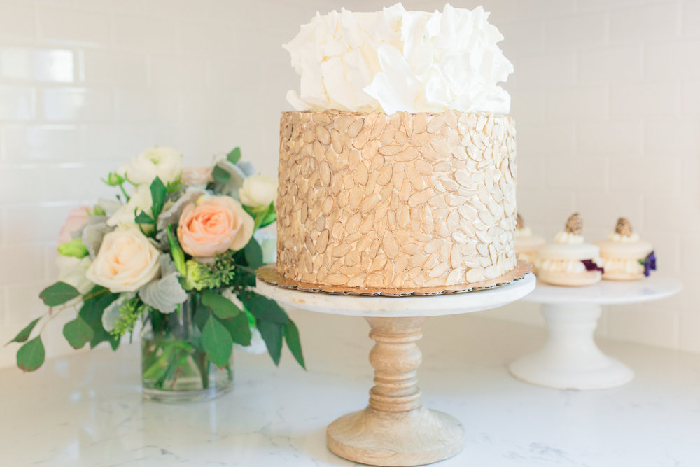 Two tiered cake: Top layer decorated with white chocolate shards, bottom layer adorned with gold dusted almond slivers. Photo:  Yasmin Roohi