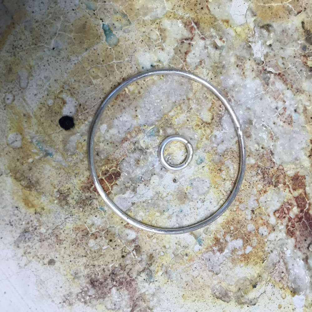 Center the soldered jump ring within the larger circle.
