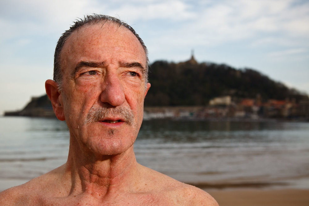 Year-round swimmer Ovidio on La Concha beach, with Monte Urgull in background,  San Sebastián, Spain.