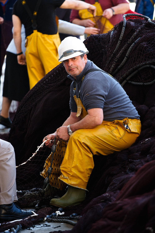 Fisherman repairs nets in harbour, San Sebastián, Spain.