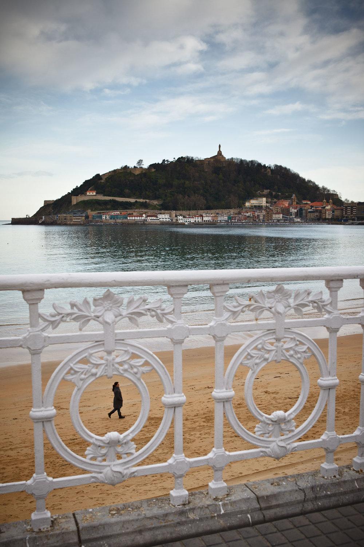 Dogwalker on La Concha beach with Monte Urgull in background,  San Sebastián, Spain.