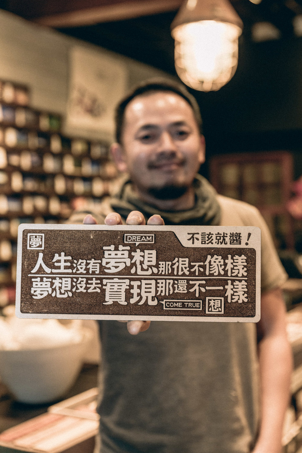 "Yang holding up one of his favourite works.  ""If you don't have a dream in life, that shouldn't be the way.  But if you did not fulfil your dream, that's not the same."""