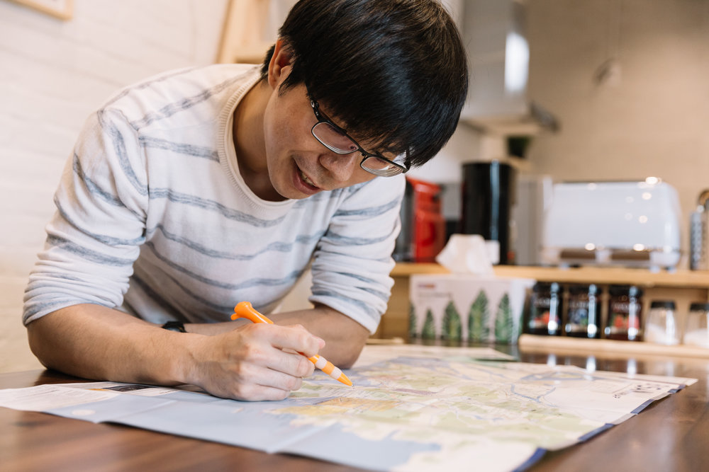 Glysen marking out the places of interest on a map of Busan. This is what he does daily for his guests.