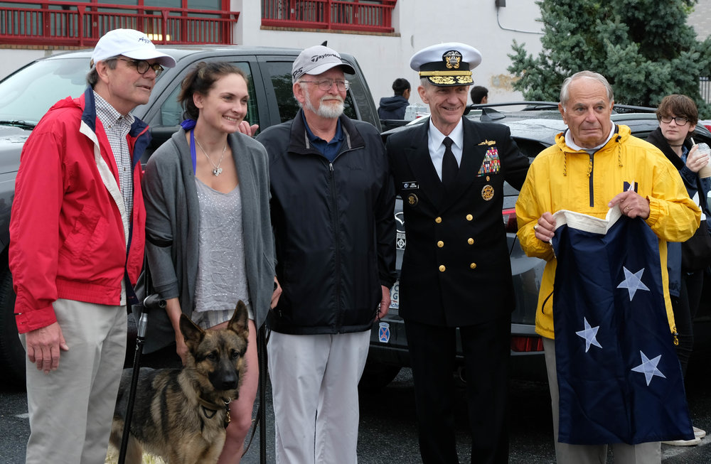 Some of the participants include Admiral Collum, retired General Barnes, and a startled Howard Brooks, who for the first time will fly the flag of a three-star admiral on  Lunar Lady , his Selene 40. The young woman lost her right leg in action, but her service dog stays close to her side so you might not even notice.