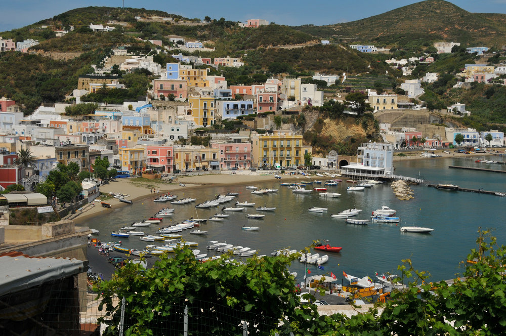 The small boat harbor at Ponza borders the larger fishing boat and commercial harbor. These boats are mostly rental boats.  Egret's  dink is pulled up on the beach in front of the bright coral house left center.