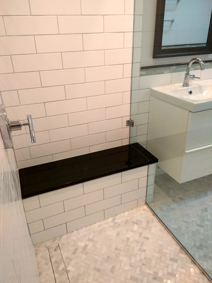 The absolute black granite bench matches the trim that circles the rest of the room. The slot drain can be seen as well - there is no curb, only a slight pitch to allow the water to run back to the slot drain.