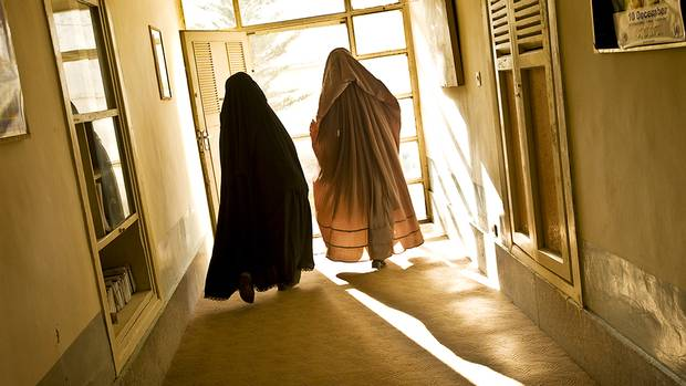 Women don burkas on their way out the door. Although many women in Kandahar do not often venture outside their home compound walls, on the rare occasion when they do they cover from head to toe. (Paula Lerner/Aurora Photos)