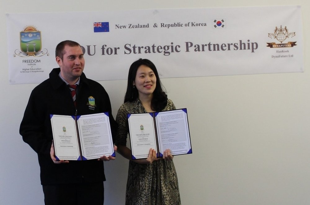 Rachel, S. YOO, the President of HanKook DynaFuture and Eliot Henderson a Director of FREEDOM hold copies of the new MOU