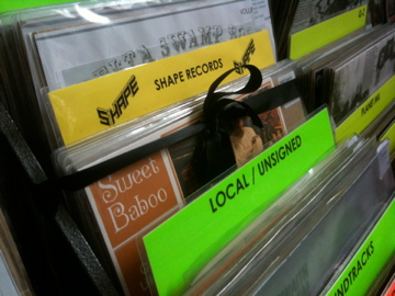 "One of our stated aims when we set up Shape was to get our own section in Spillers Records, Cardiff so that we would no longer be in the 'local / unsigned"" section. We achieved this goal in 2011. We got to cut the black ribbon to officially 'open' it."