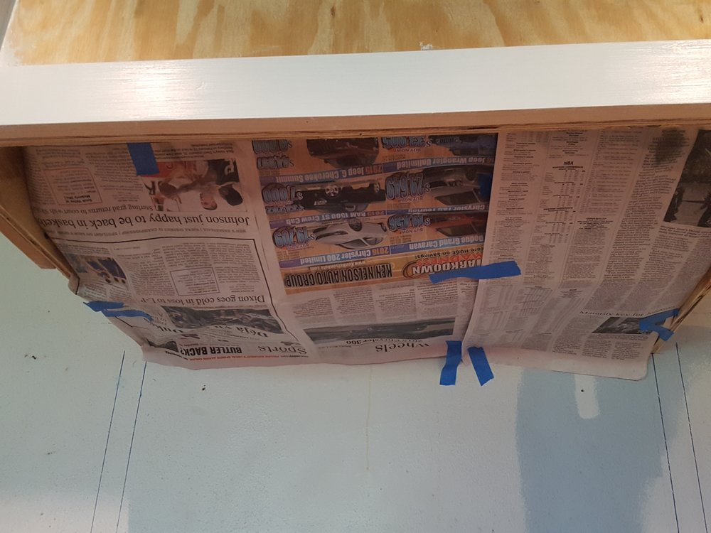 I used painters tape and newspaper to protect my new range hood while I spray varnished the inside.