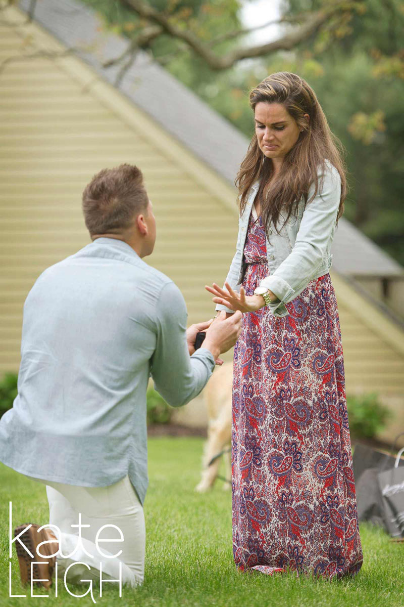 Newly engaged girl looks at new ring while fiance is down on one knee