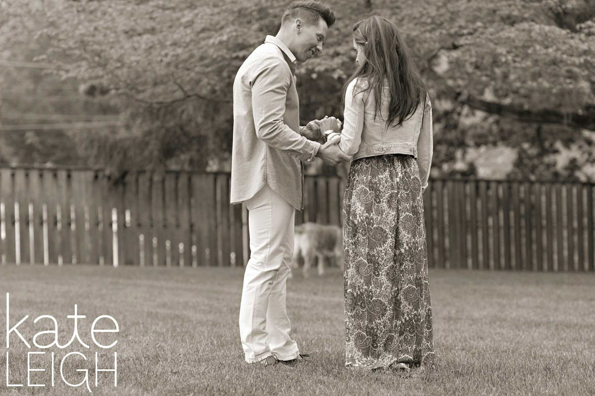 black and white of newly engaged couple looking at new engagement ring