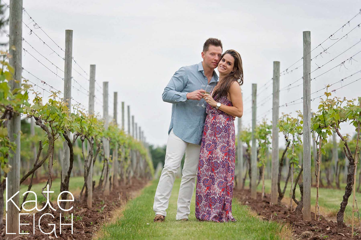 engaged couple cheers wine glasses at crossing vineyards winery