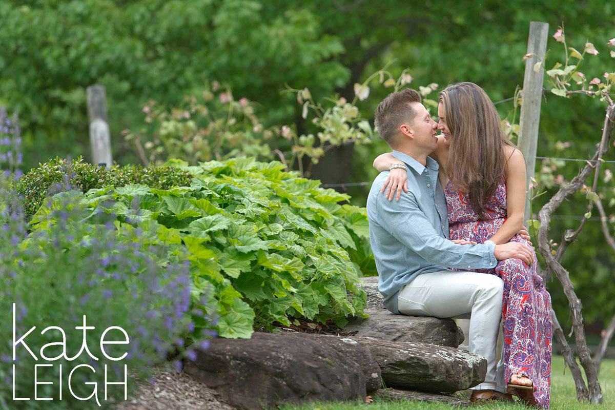 engaged couple sit at crossing vineyards winery in an embrace