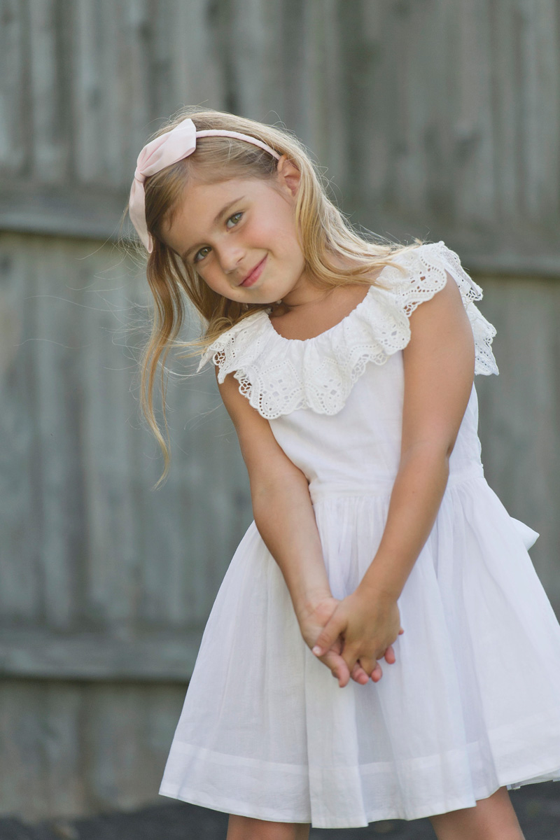 five year old girl in front of fence in white dress