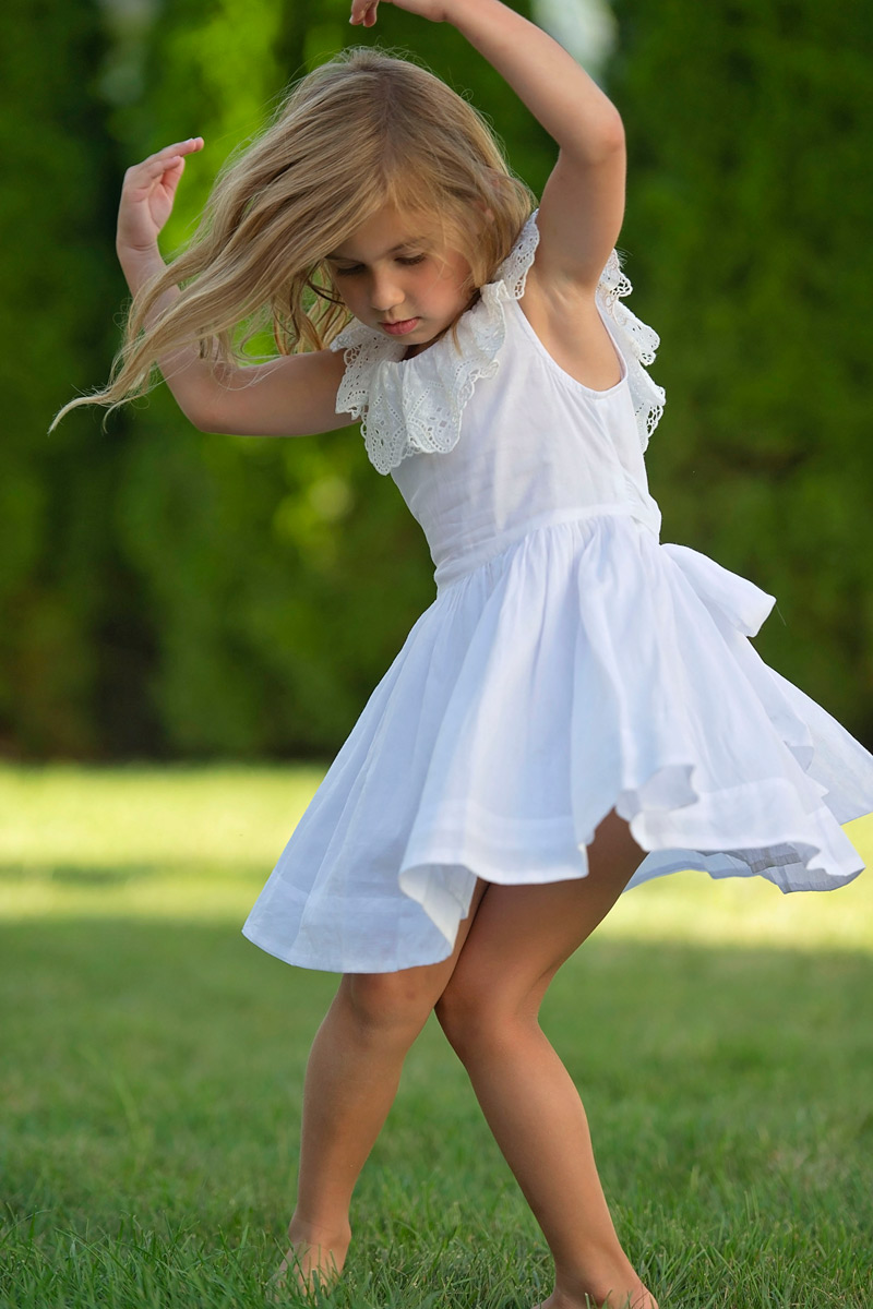 five year old dancing in the backyard in white dress