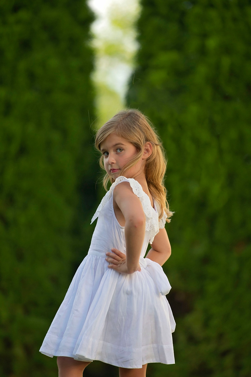 five year old girl in backyard with white dress