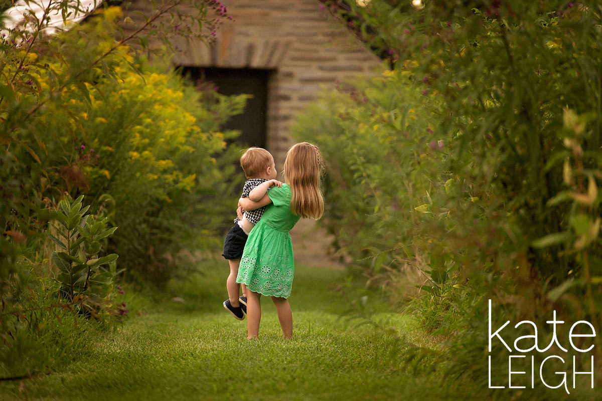 little girl carrying little brother down a path from behind