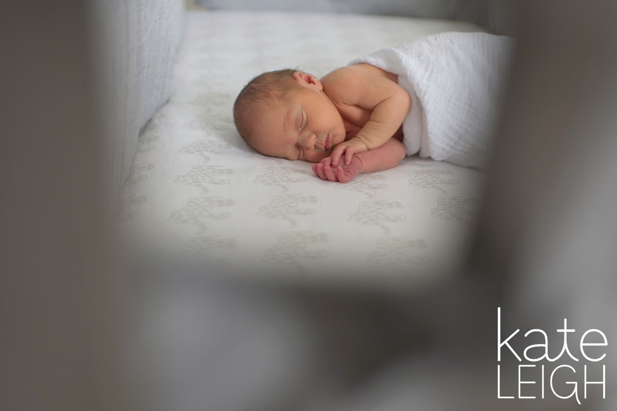 sleeping newborn seen through the crib rails