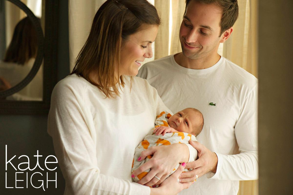 new parents cuddling newborn baby