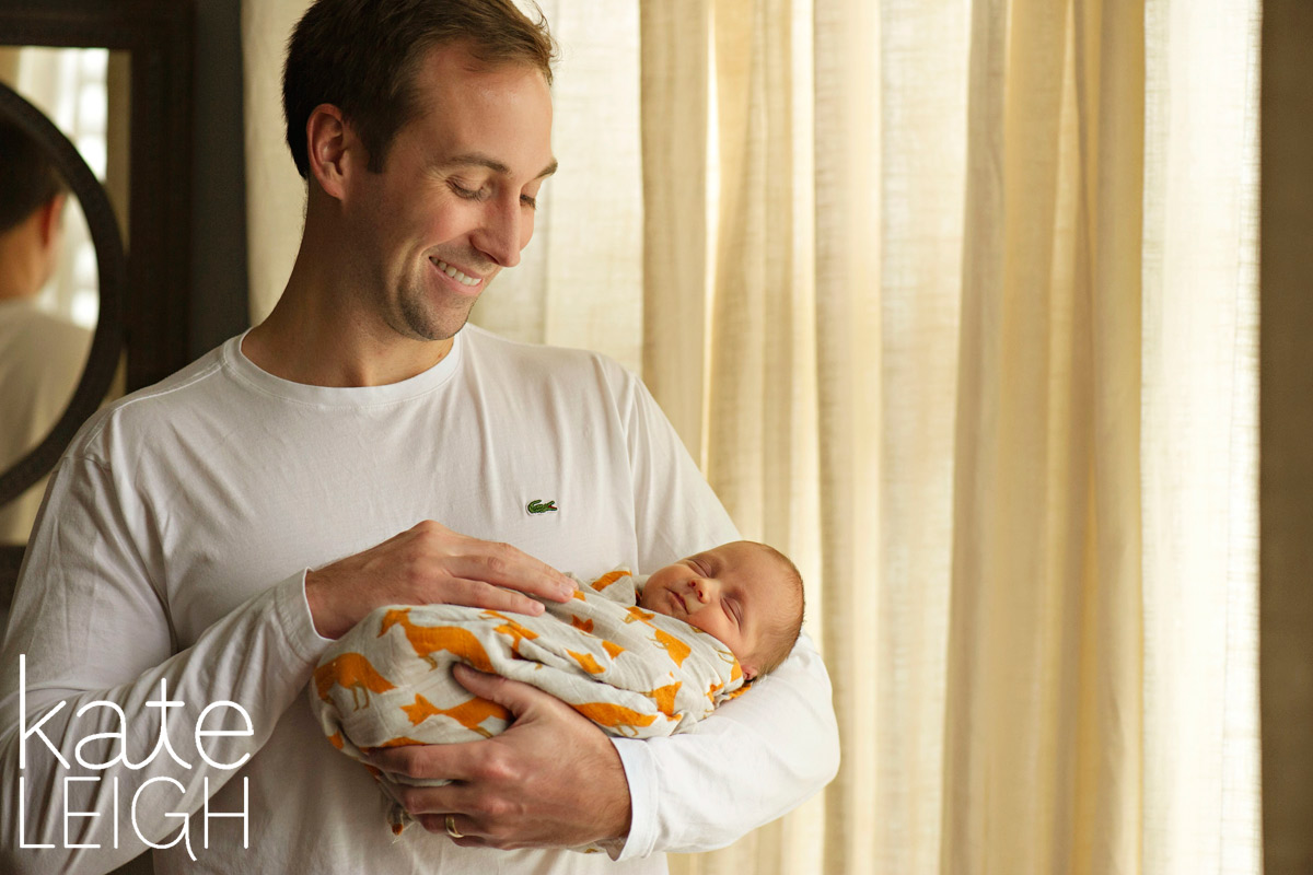 new dad holding baby boy wrapped in fox swaddle