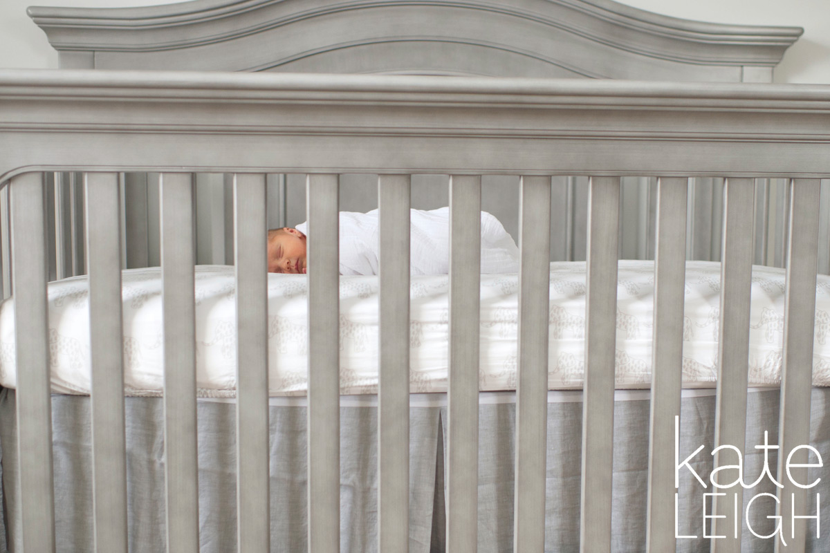 tiny newborn baby in big crib