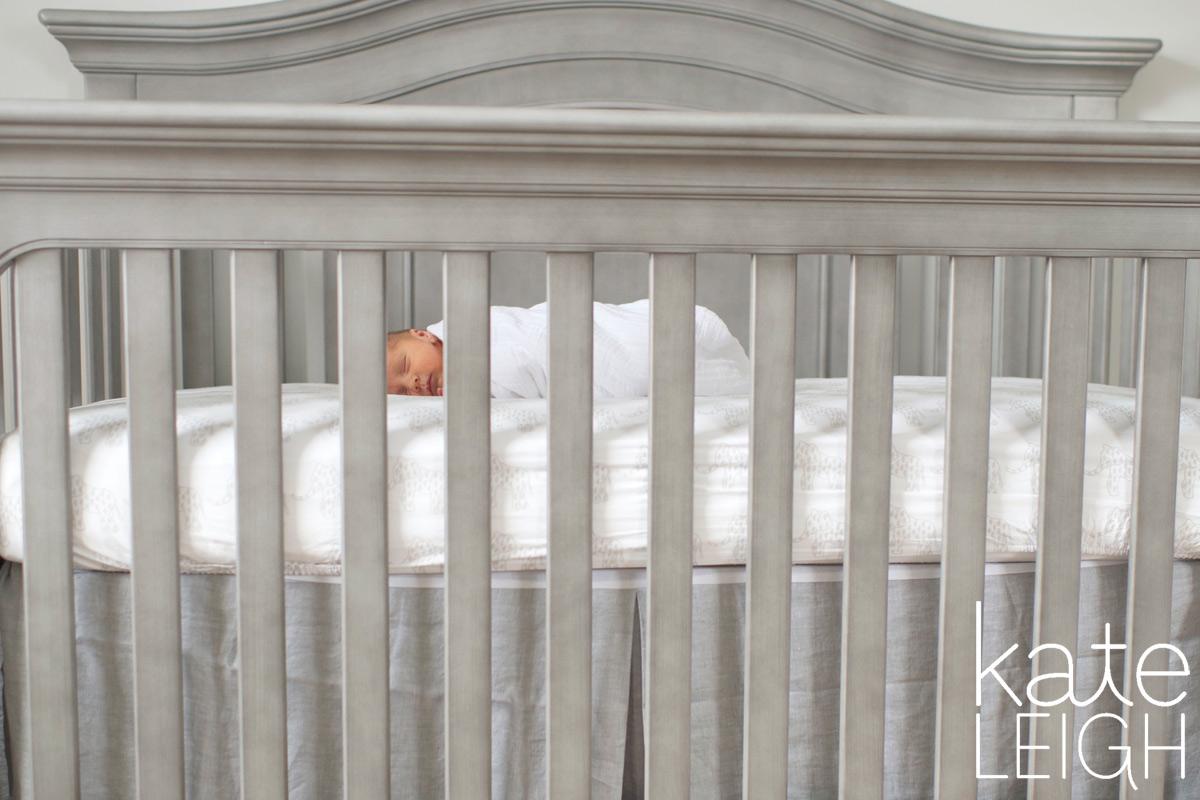 tiny newborn baby in big crib