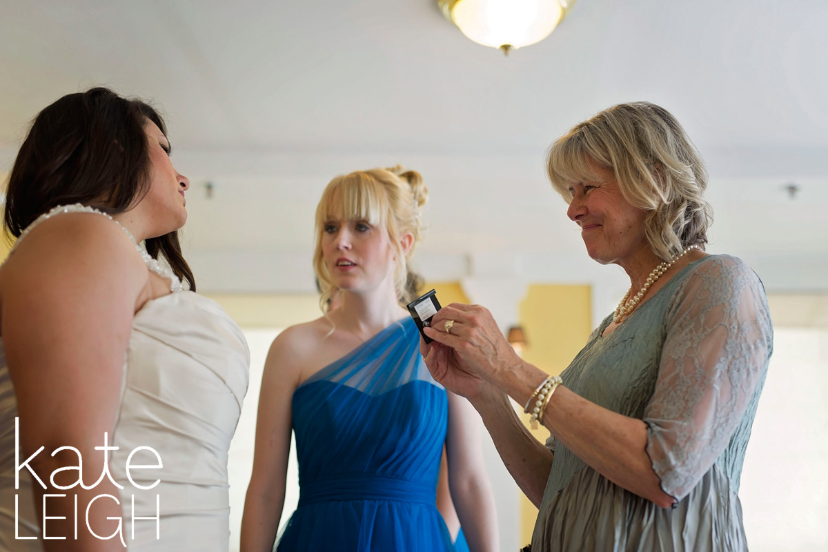 Tearful mother of the bride about to help bride put on her earrings