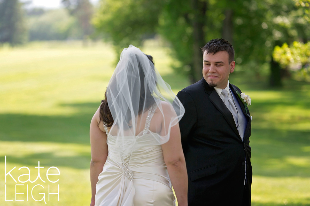 Groom seeing his bride for the first time during a first look on a golf course