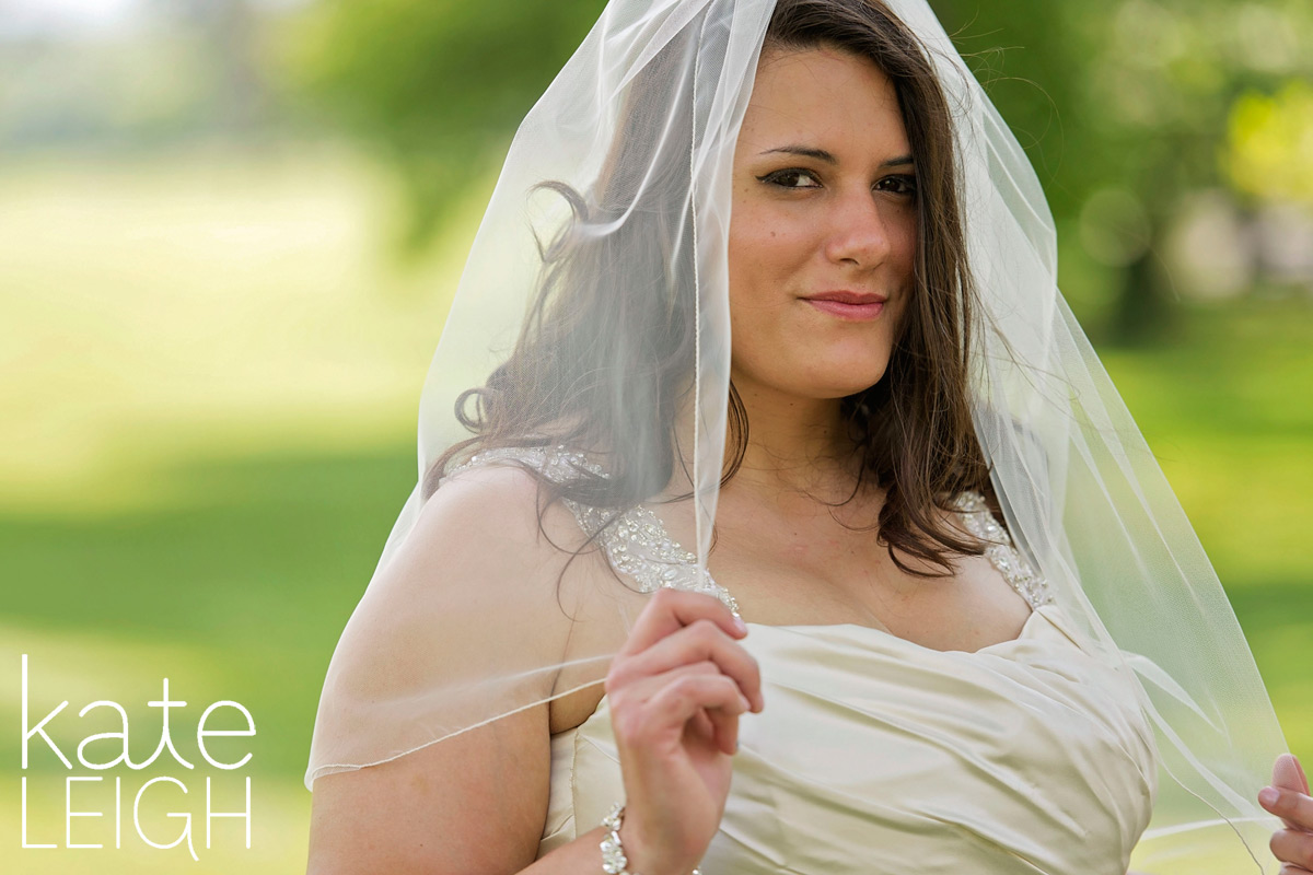 Bride holding onto veil with fingertips and looking into camera
