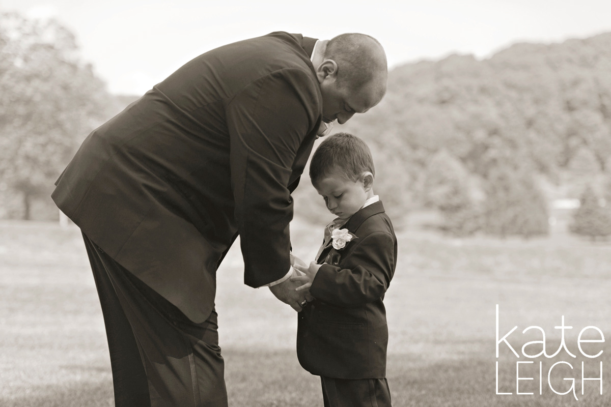 Father helping little boy button his tuxedo on a golf course