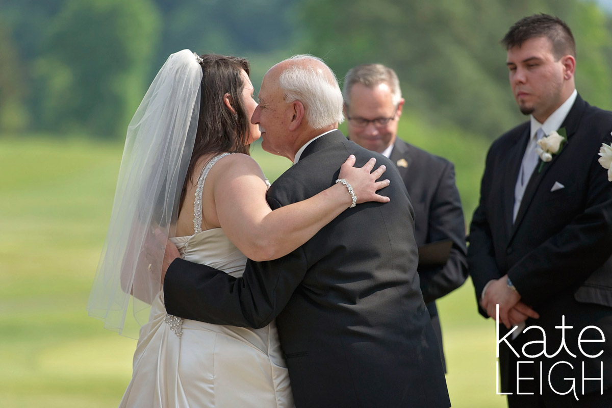 Father kisses his daughter at the altar on her wedding date