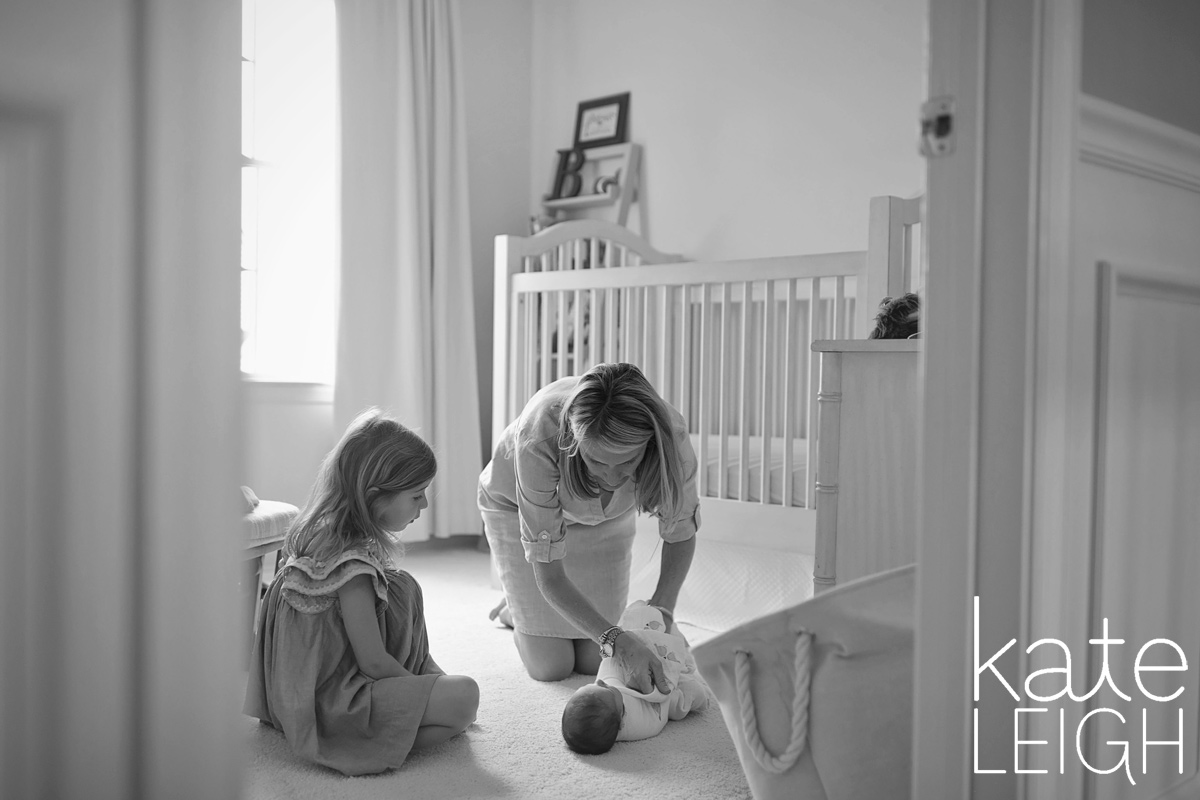 black and white image of mom changing new baby while big sister looks on