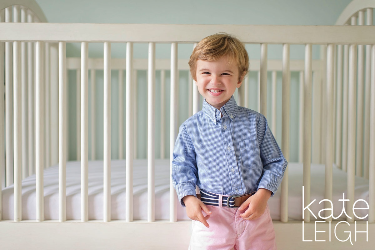 toddler boy smiling in front of his crib