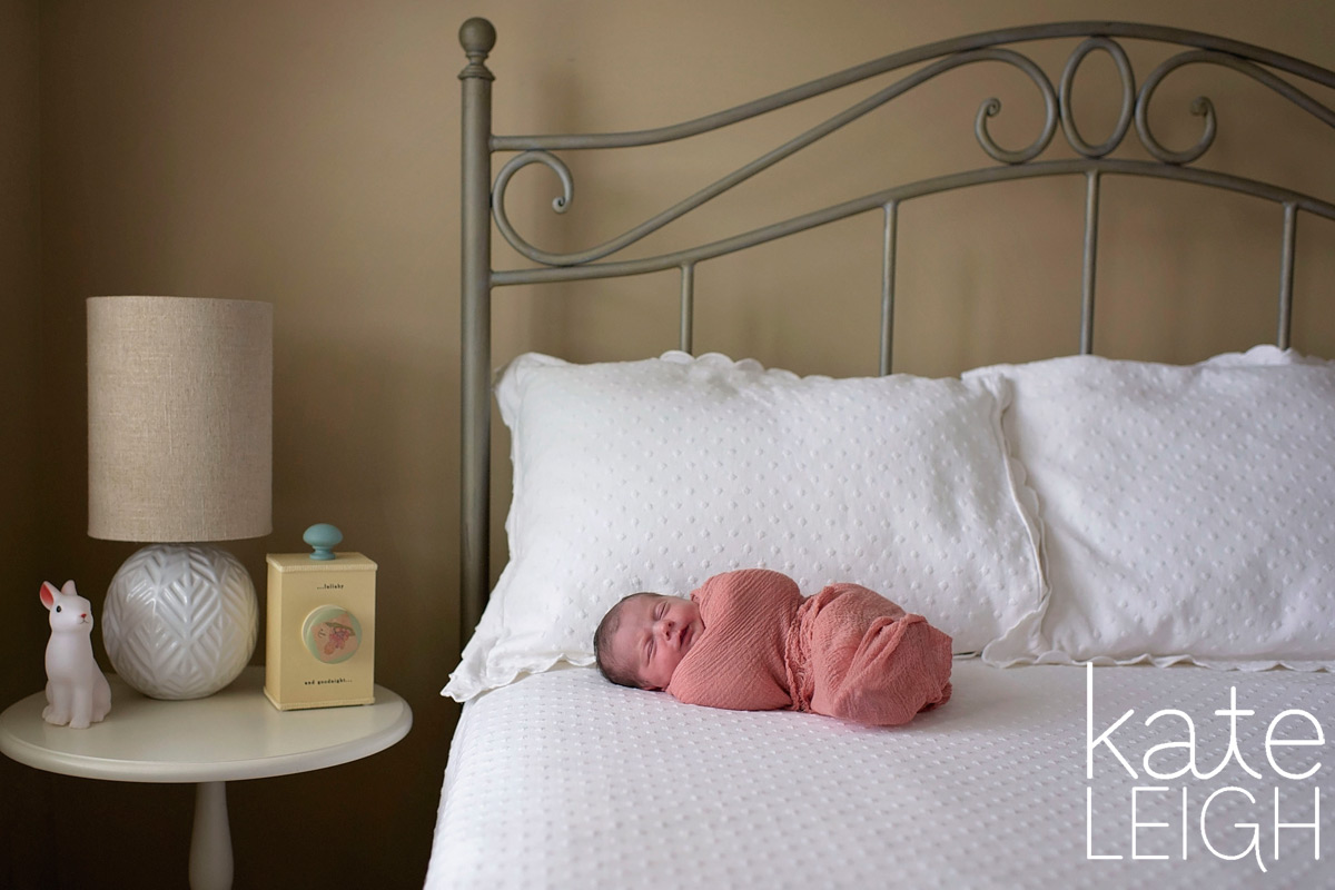 baby swaddled in pink on big white bed next to music box
