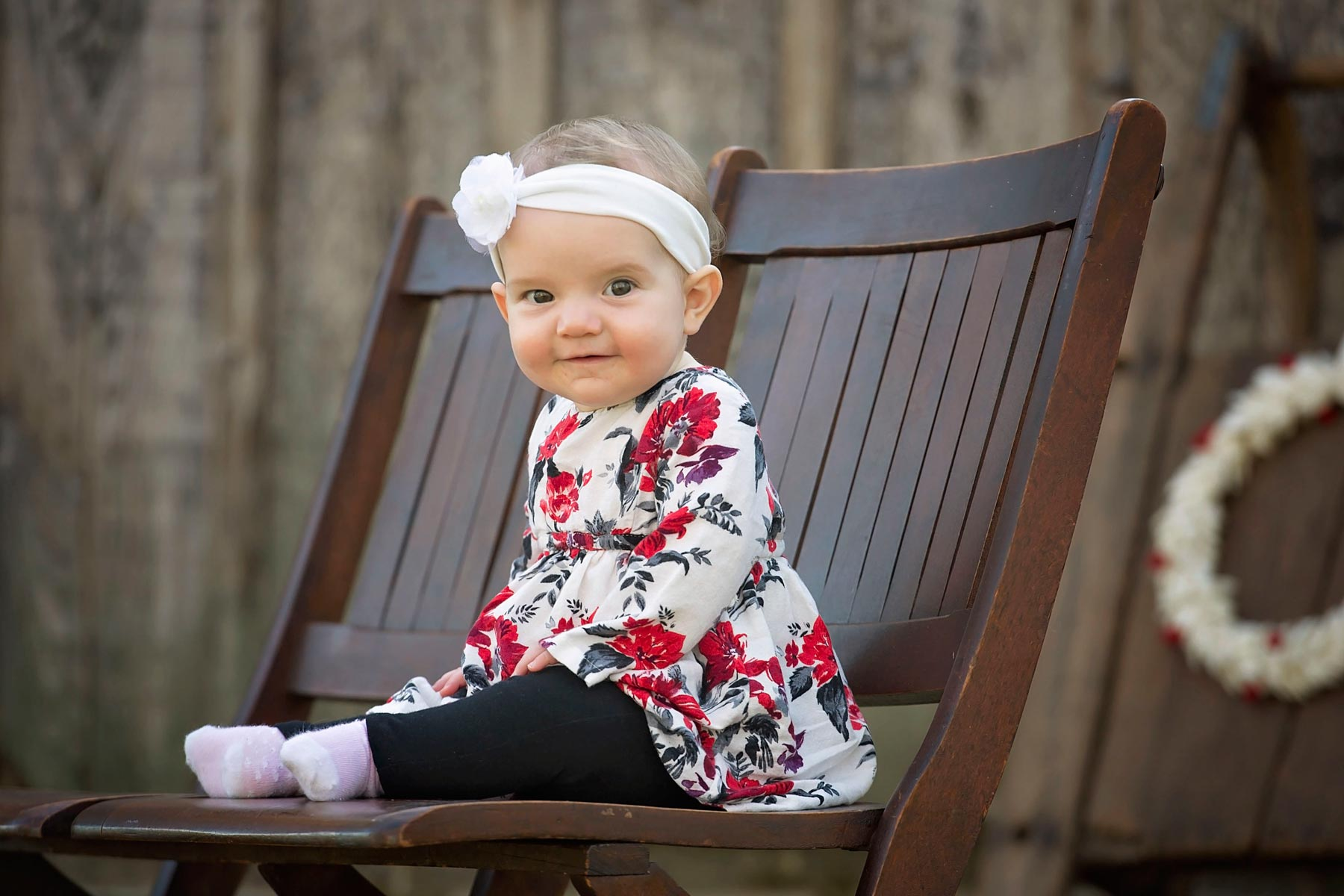 baby in floral top sits on bench looking to her left at camera