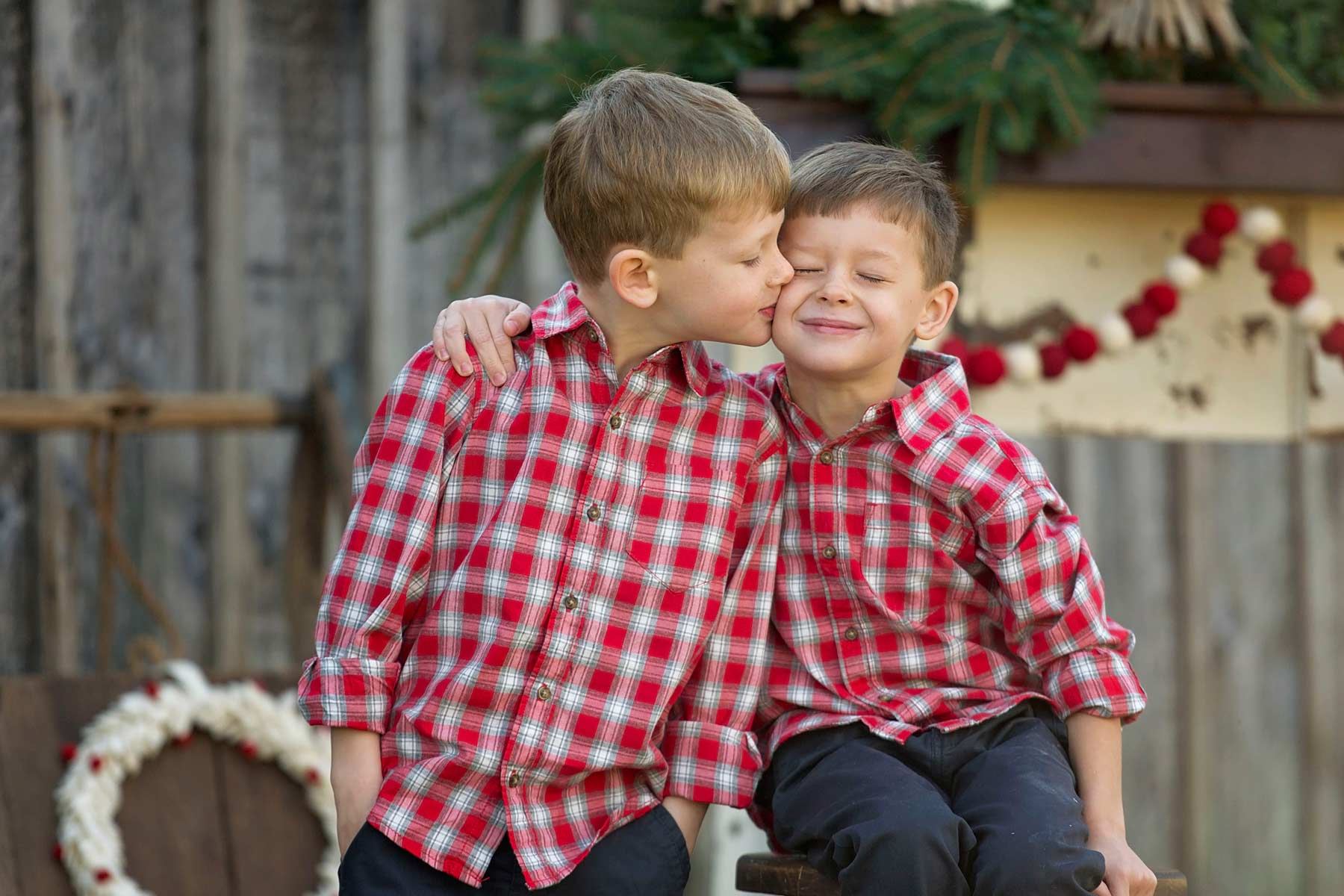 twin boys in red plaid snuggle in holiday themed setup