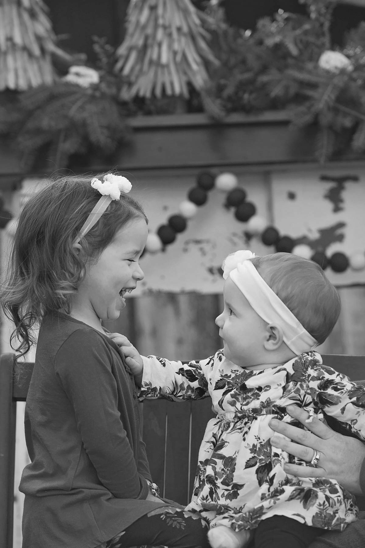 black and white of two sisters looking at each other and smiling and laughing