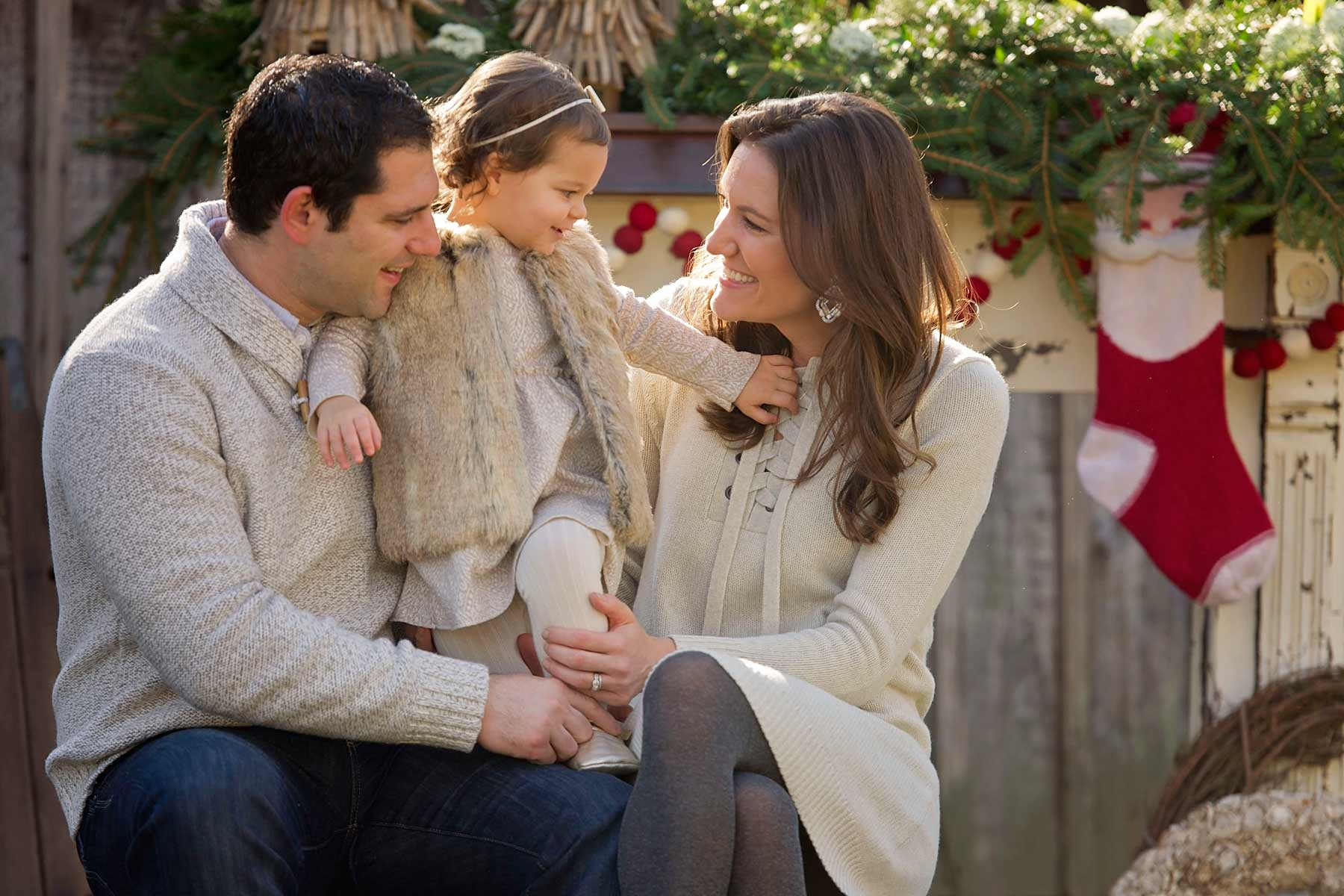 family in neutral outfits sit on trunk in holiday scene looking at daughter