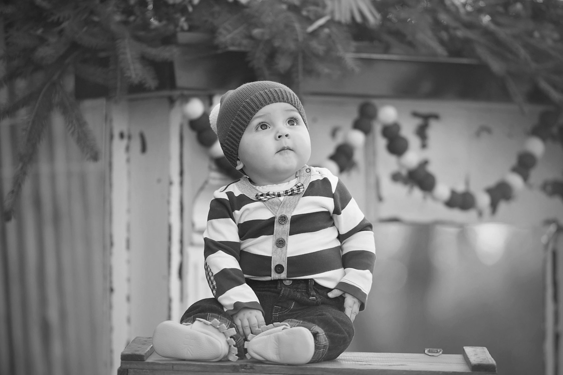baby boy in red and white stripes looks up to the sky in front of holiday mantel